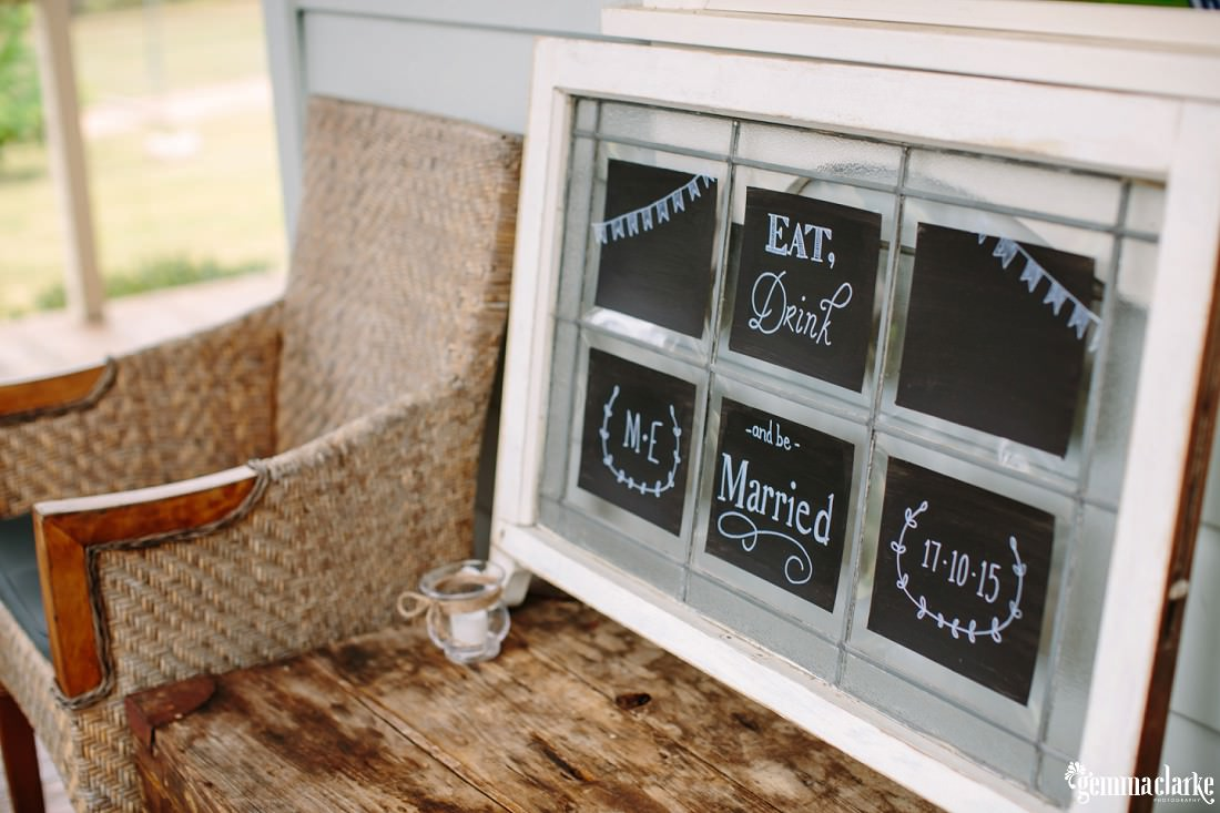 "An ""Eat, drink and be married"" sign on small chalkboards in a frame on a wooden bench next to a wicker chair"