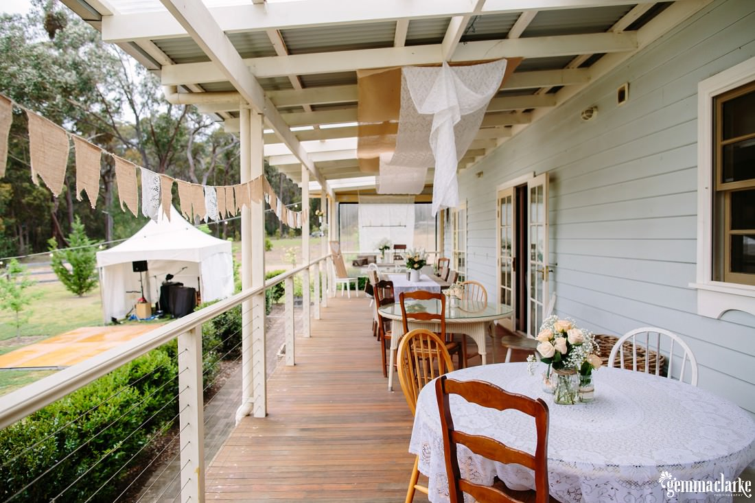 Wedding reception setup with mismatched tables and chairs, rustic looking decorations with hessian and lace bunting, on a cottage verandah