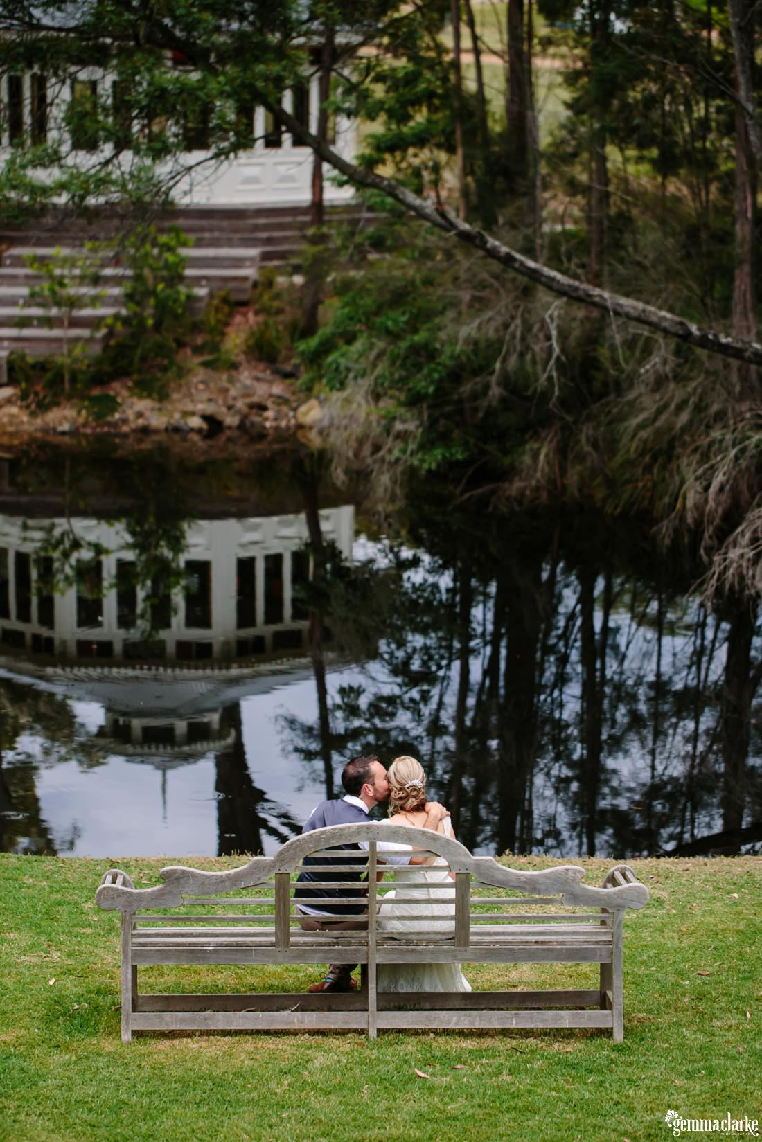 A groom kisses his bride on the cheek as they sit on a wooden bench seat near a small lake
