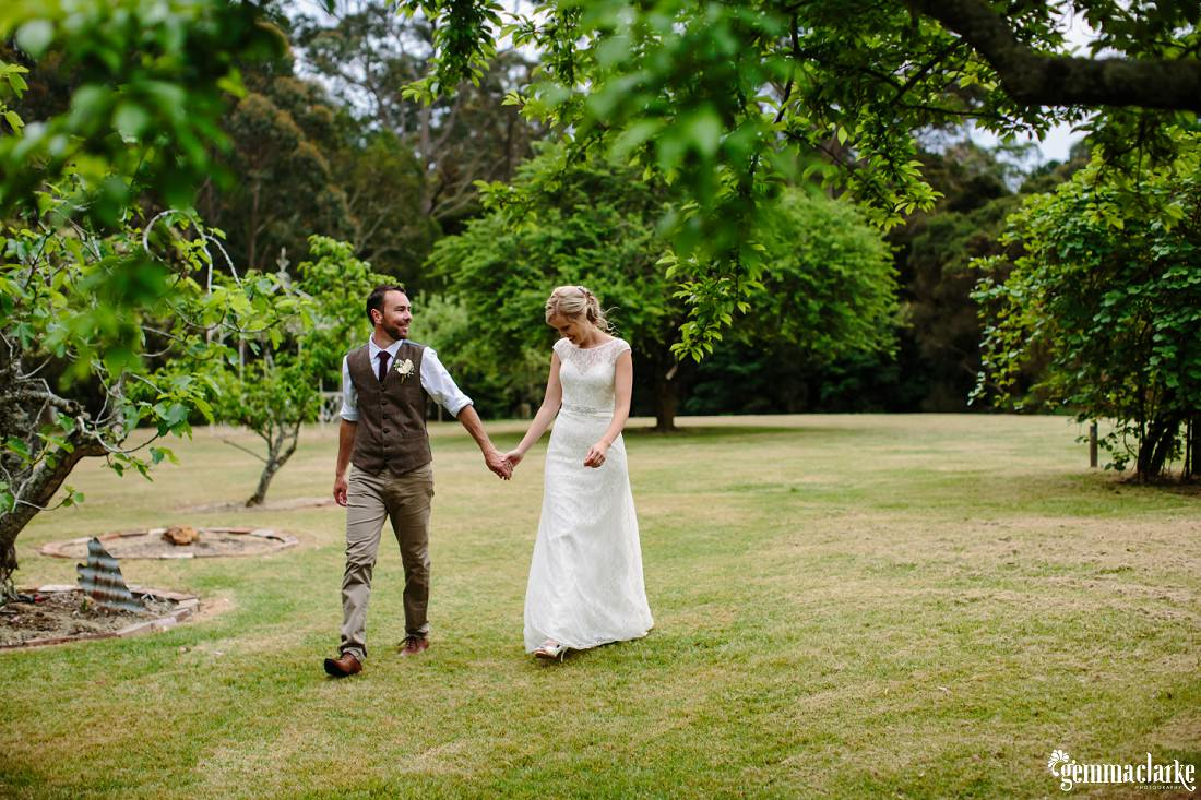 A bride and groom hold hands and walk across a lawn amongst some trees