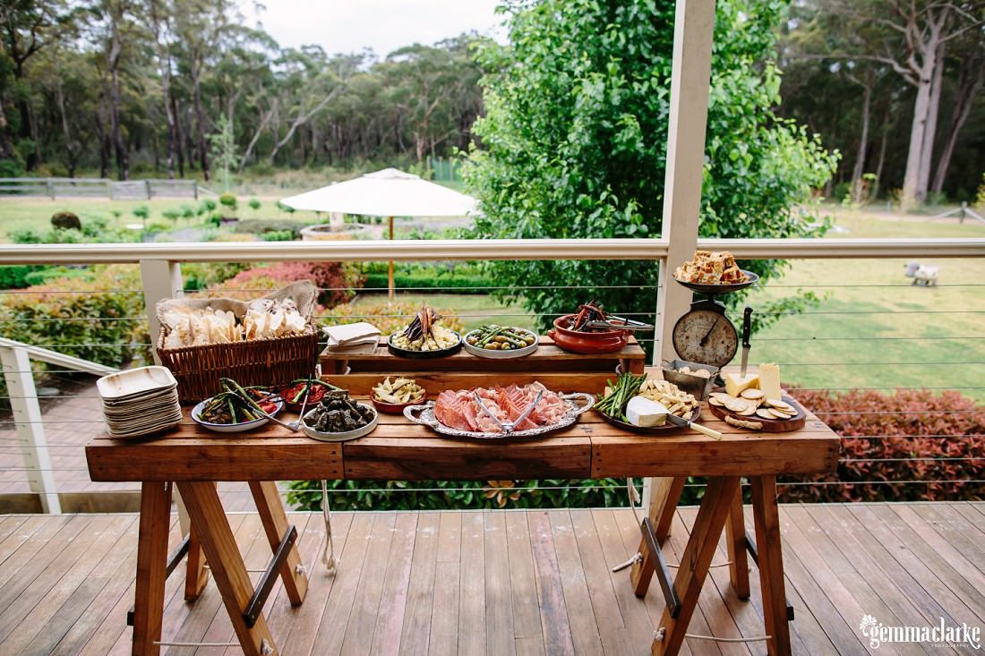 Antipasto platters on wooden tables on a verandah