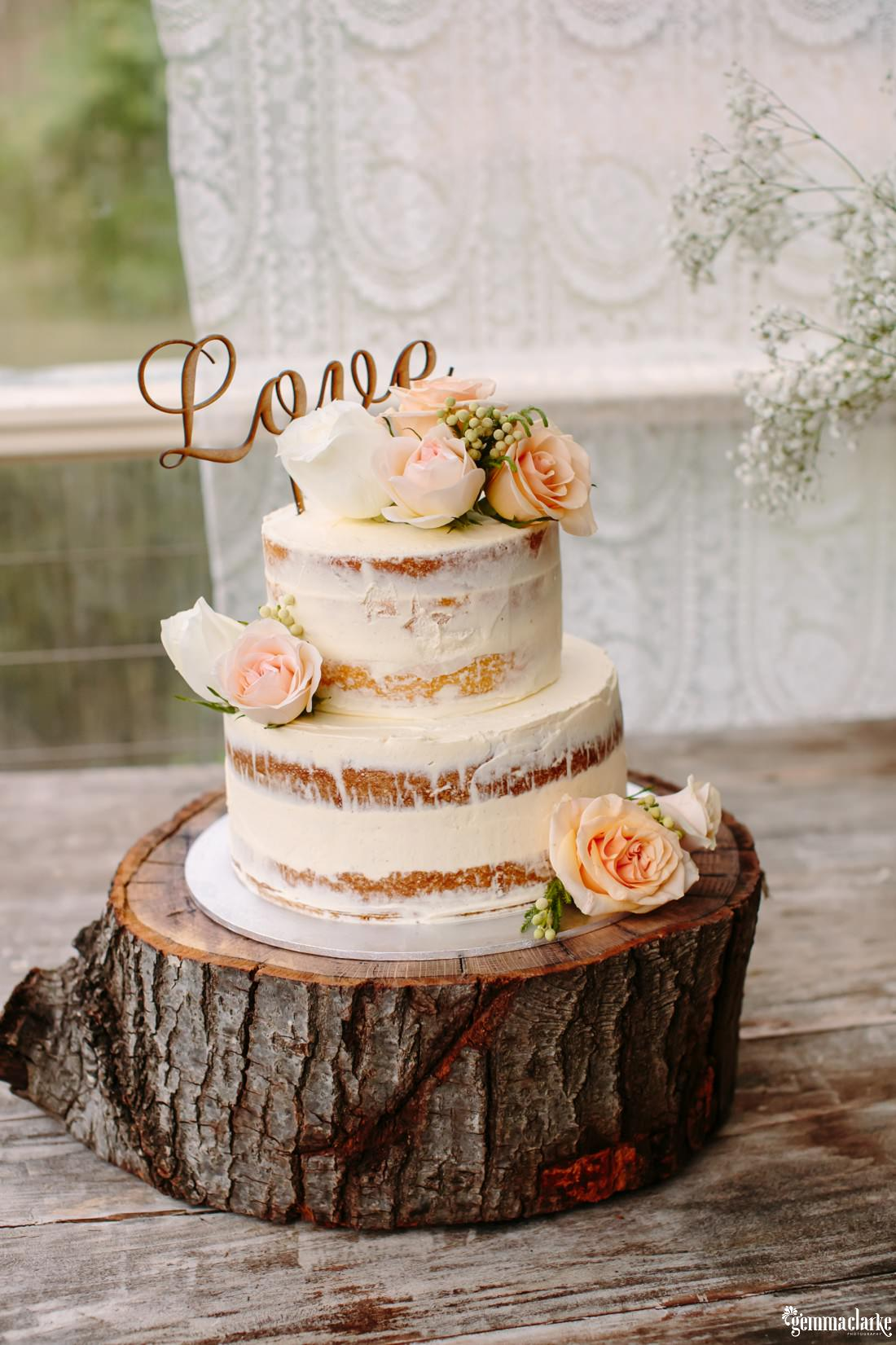 "A white two tiered wedding cake on a wooden log platter with floral decorations and a ""Love"" topper"