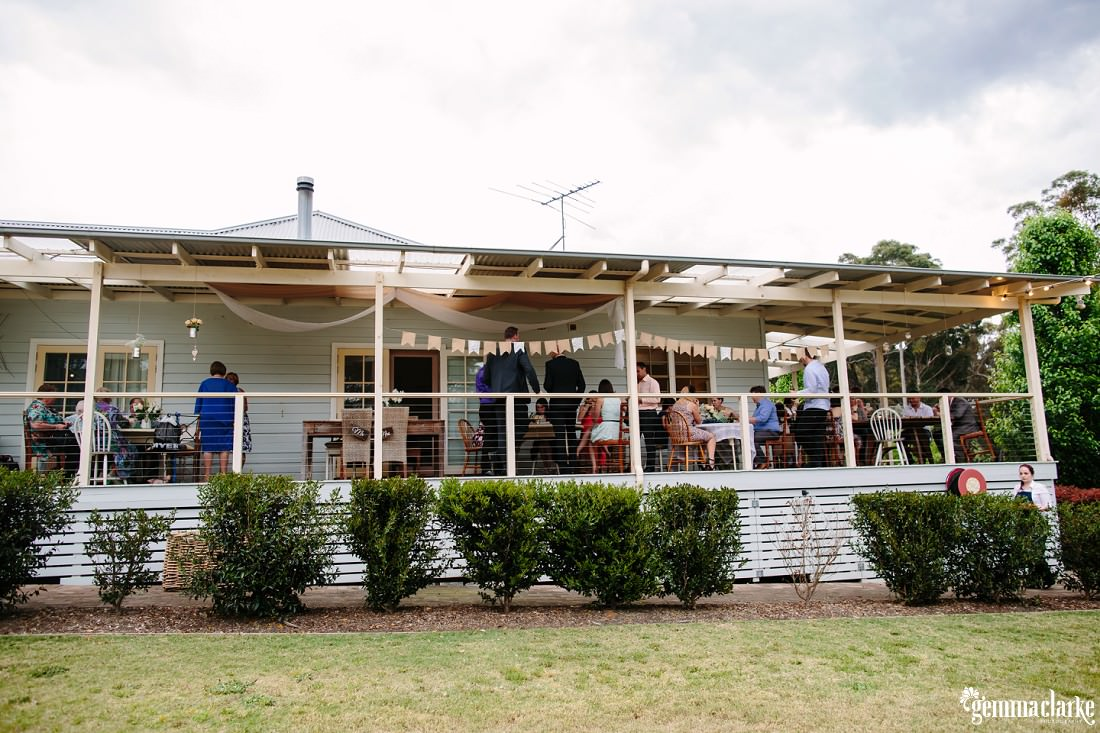 Wedding guests mingling on a cottage verandah