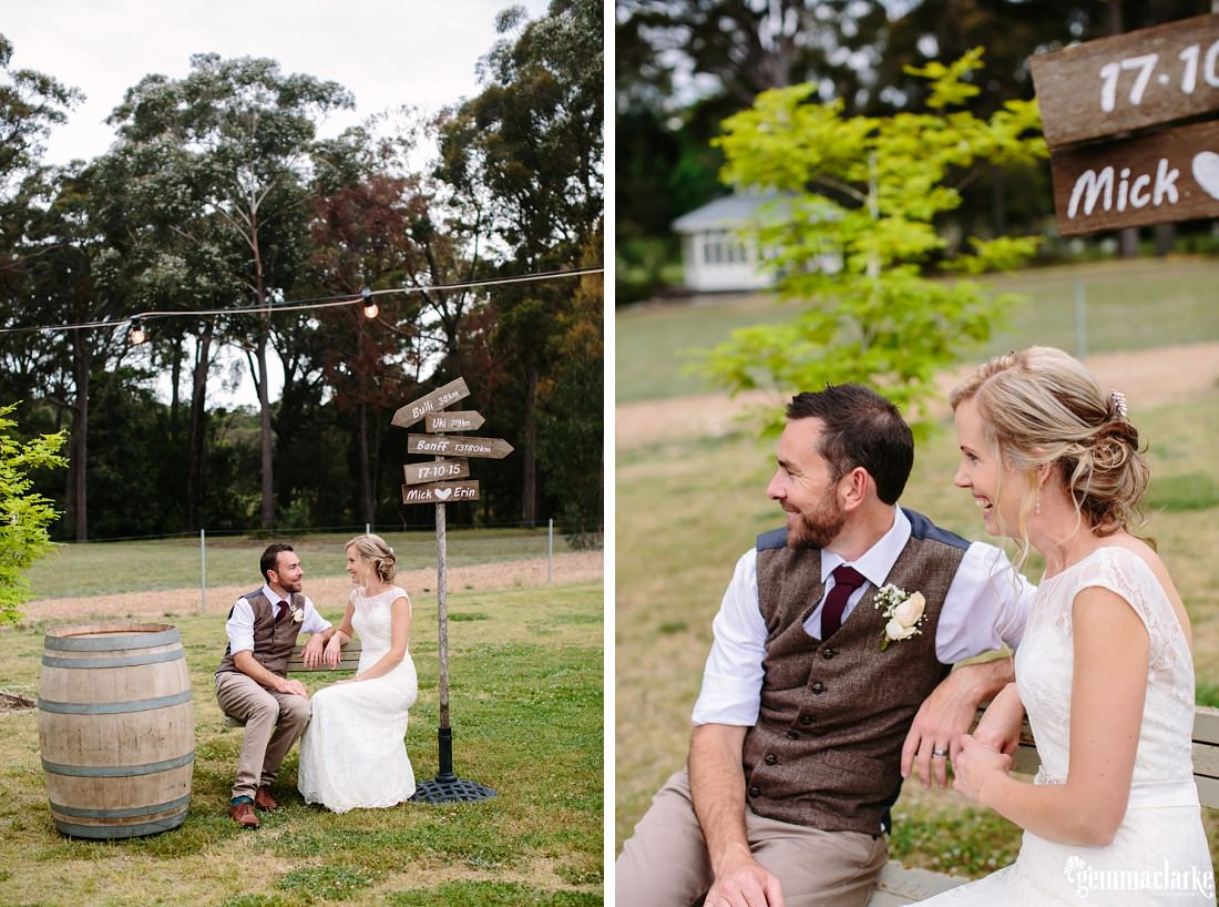 A bride and groom sit with each other on a wooden chair next to a wooden signpost and wooden barrel