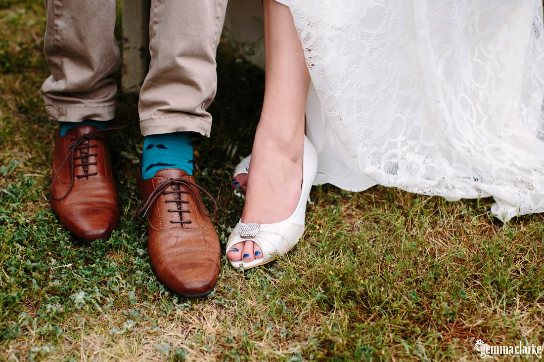 A closeup of a bride and groom's shoes on the grass