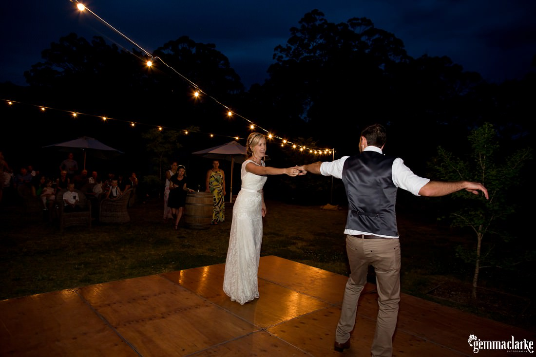 A bride and groom share their first dance under lights on an outdoor dance floor