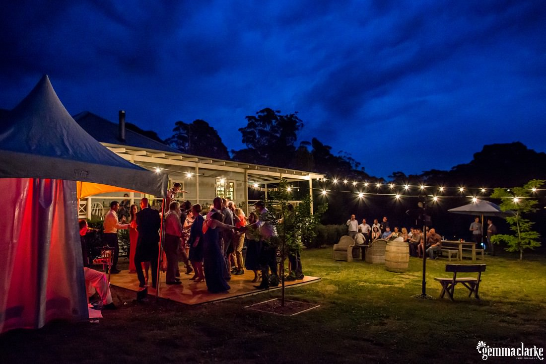 An overall shot of wedding guests dancing on an outdoor dance floor