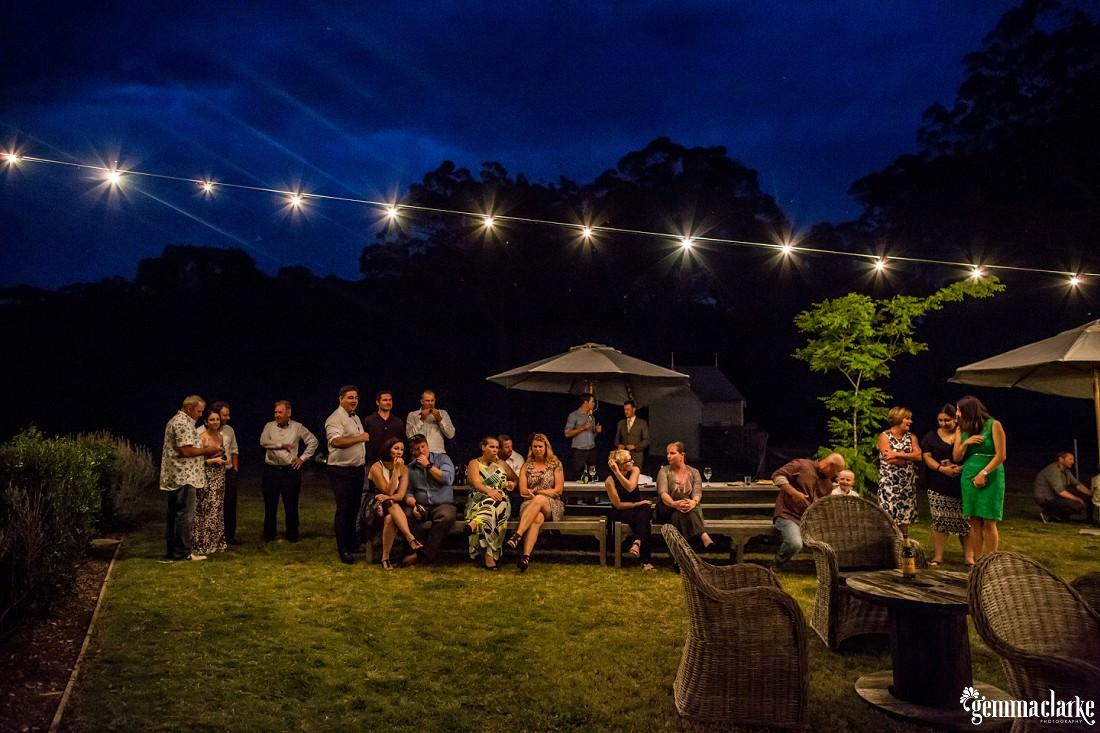 Wedding guests mingling under lights outdoors