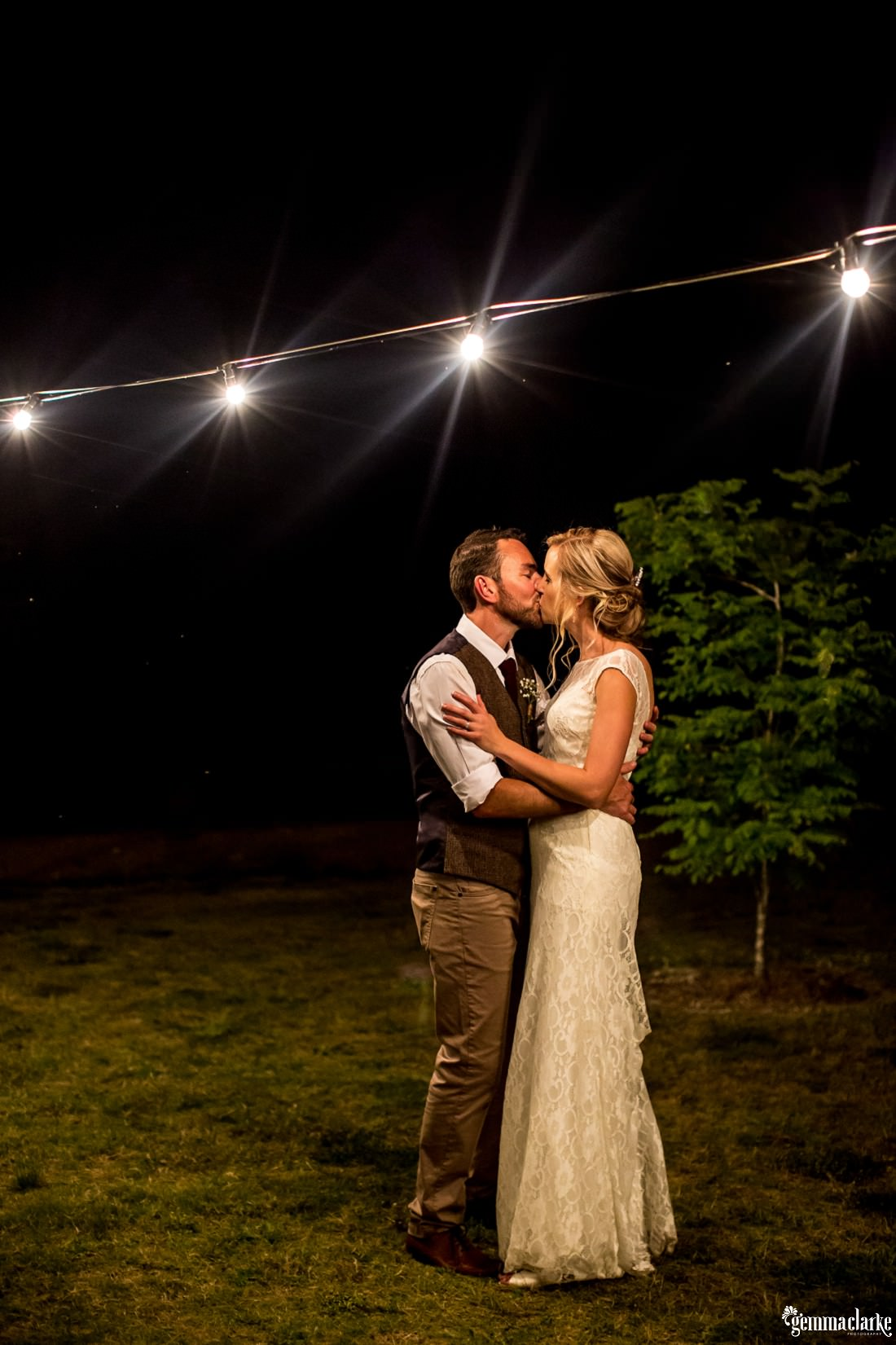 A bride and groom kiss under lights outdoors