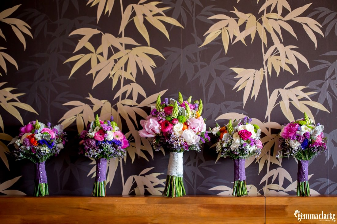 Five very colourful floral bouquets leaning against a wall