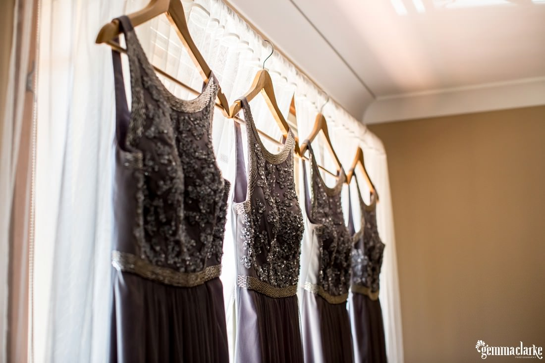 Four bridesmaids dresses on hangers hanging in a window