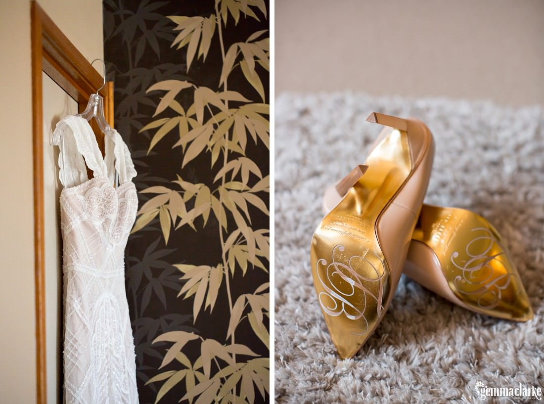 A white lacy bridal gown on a hanger in a doorway and the bright golden underside of a pair of bridal shoes