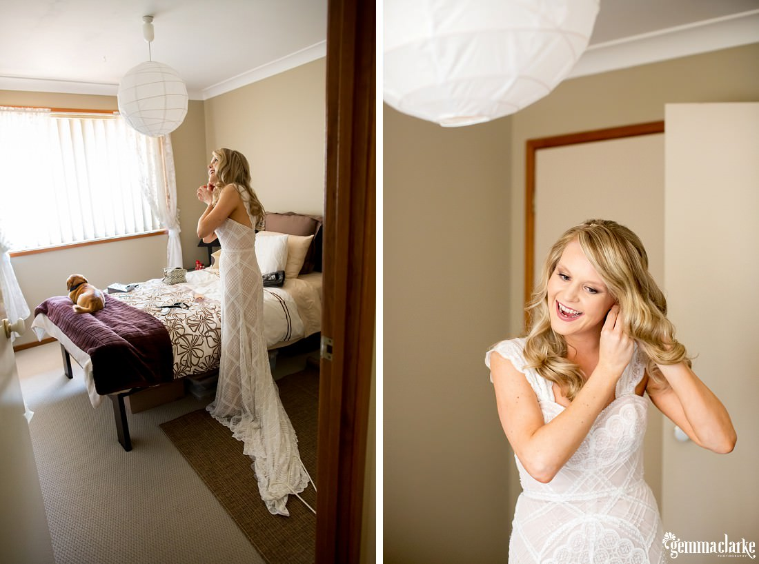 A smiling bride in her bridal gown in a bedroom putting on her earrings