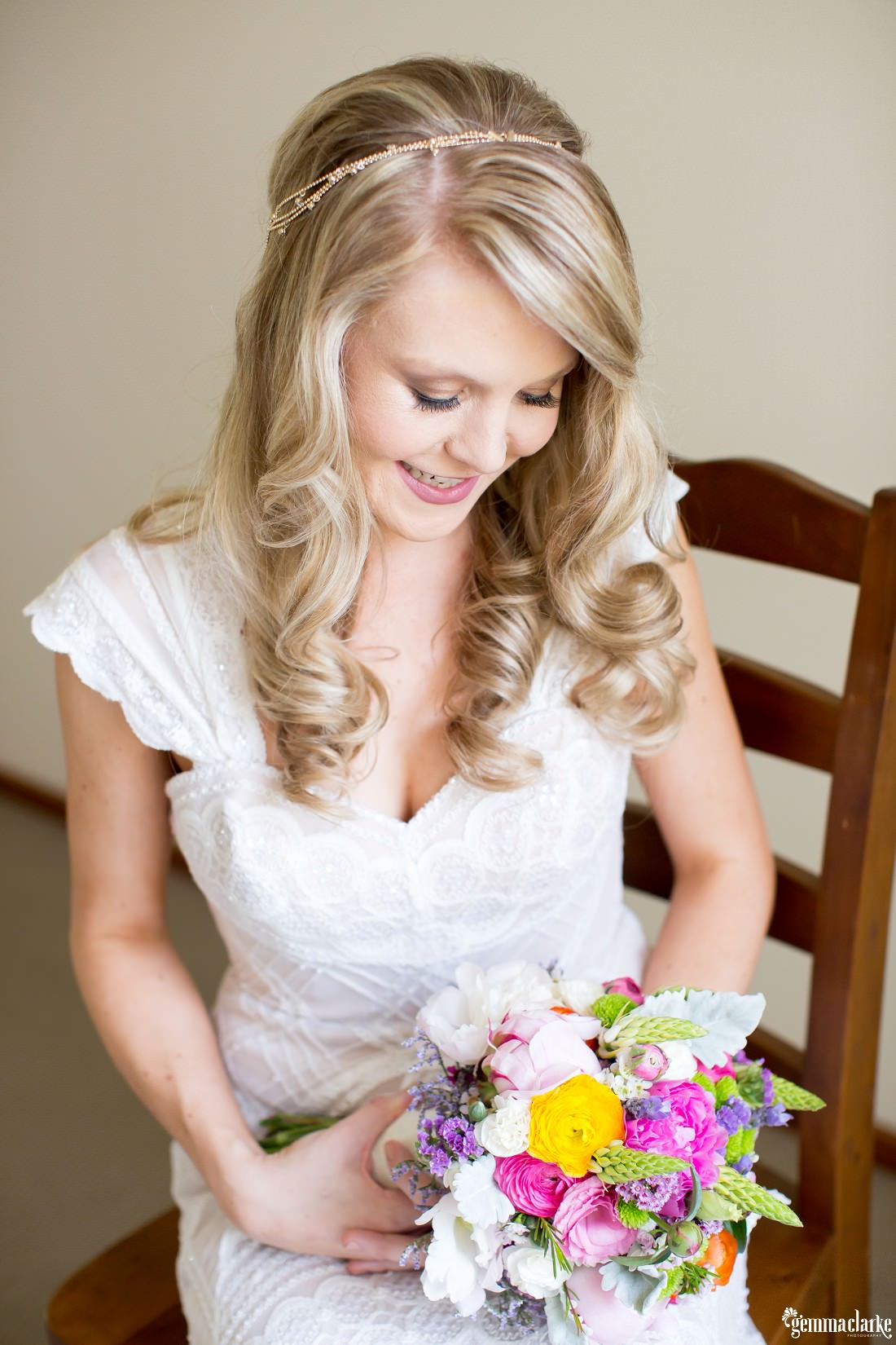 A bride in a lacy white gown sitting on a chair and looking down at the brightly coloured floral bouquet that she is holding