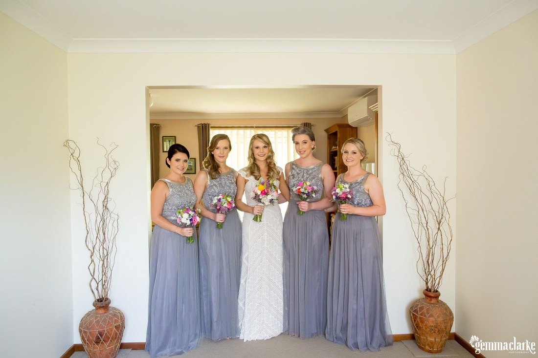 A bride and her four bridesmaids holding their bouquets and smiling while standing in a wide doorway