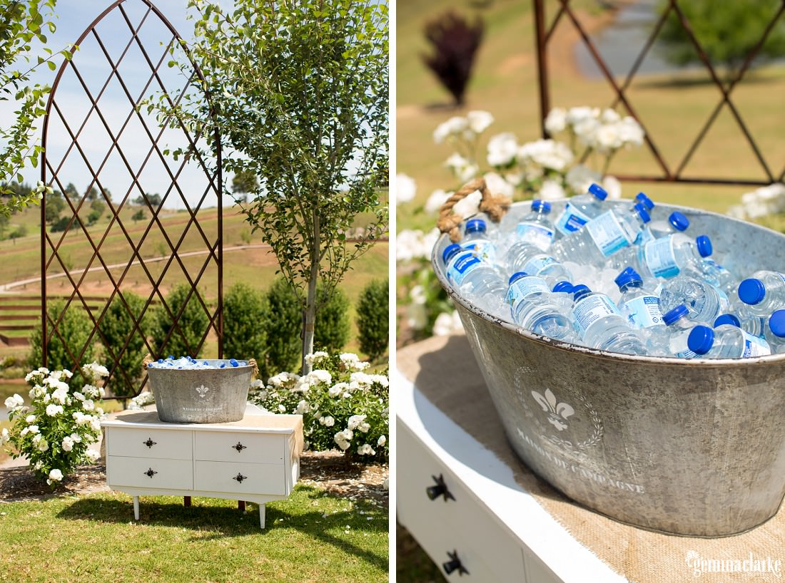 A steel bucket holding bottles of water on ice, on top of a white chest of drawers in a garden surrounded by flowers and plants