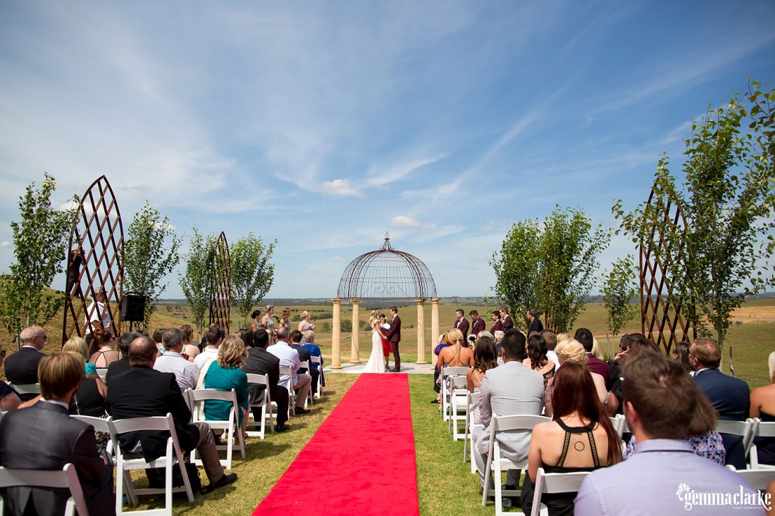 A bride and groom together under an arbour in front of a country background as their guests look on at their Sheldonbrook wedding