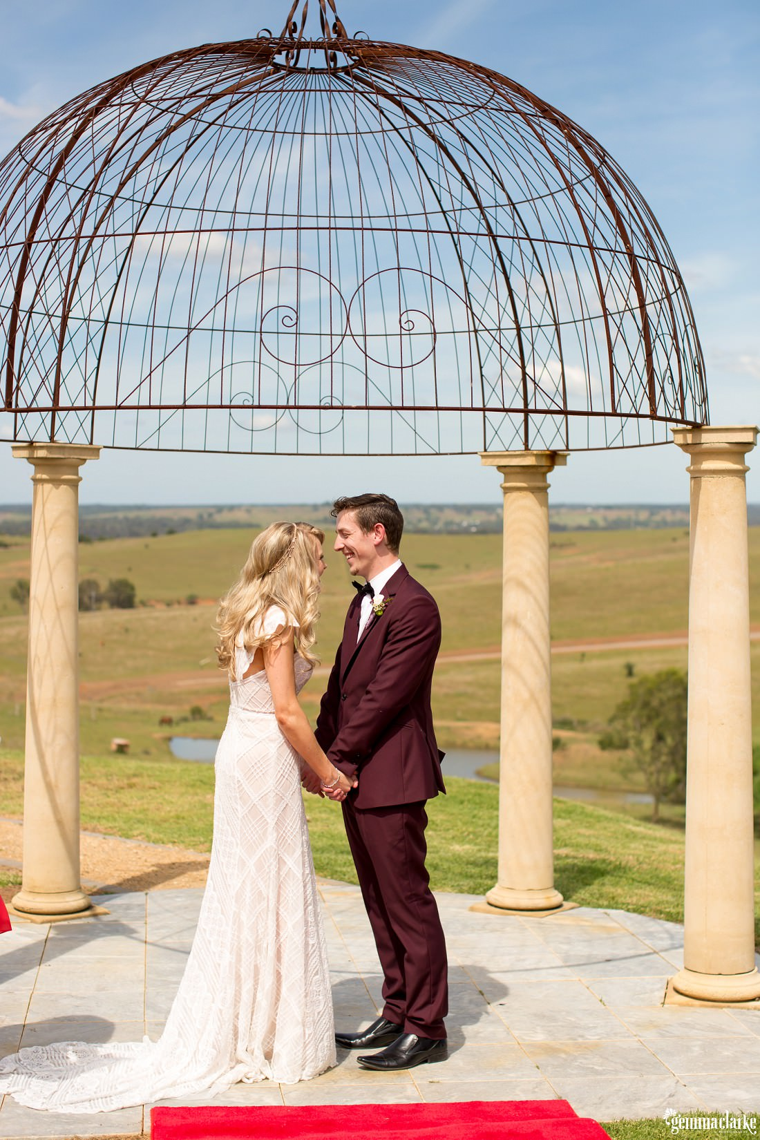 A bride and groom holding hands and smiling at each other under a steel arbour after their ceremony at their Sheldonbrook wedding