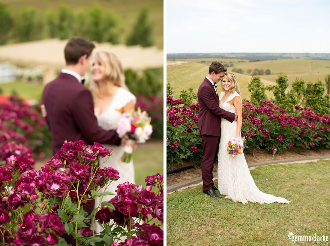 A groom holds his bride close as they stand in a garden surrounded by beautiful maroon flowers