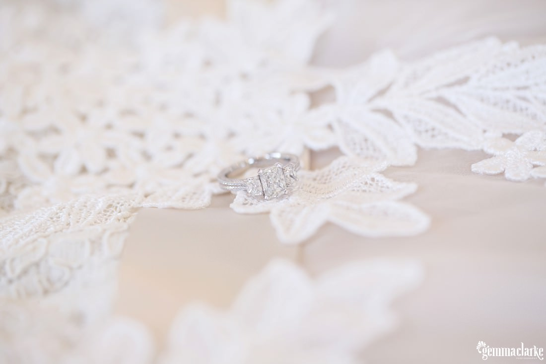 A white gold engagement ring with a lace backdrop