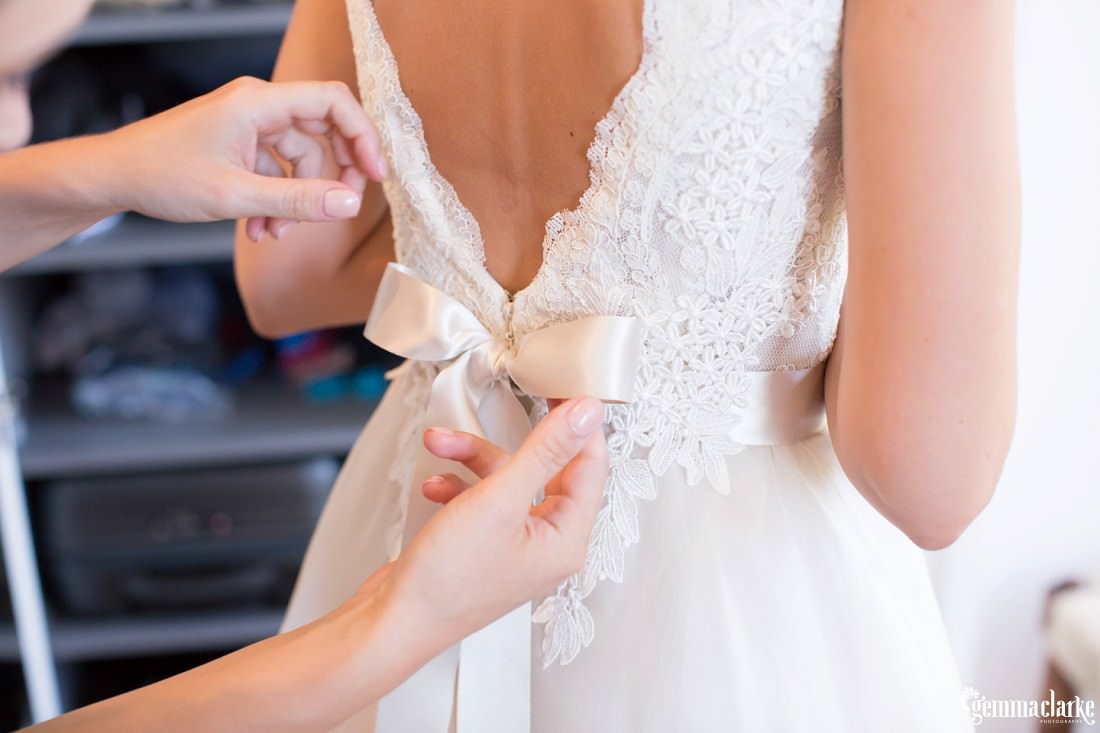 Close up of bridesmaid lacing up a bridal gown