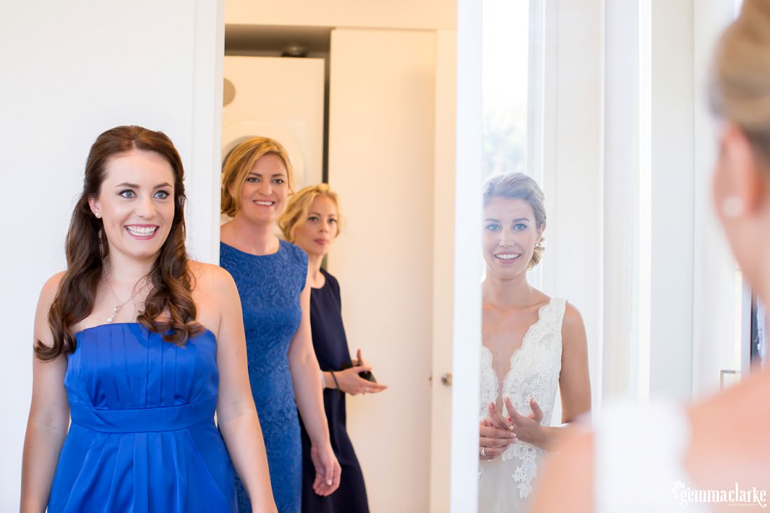 A bride sees herself in a mirror as her bridesmaids smile in the background