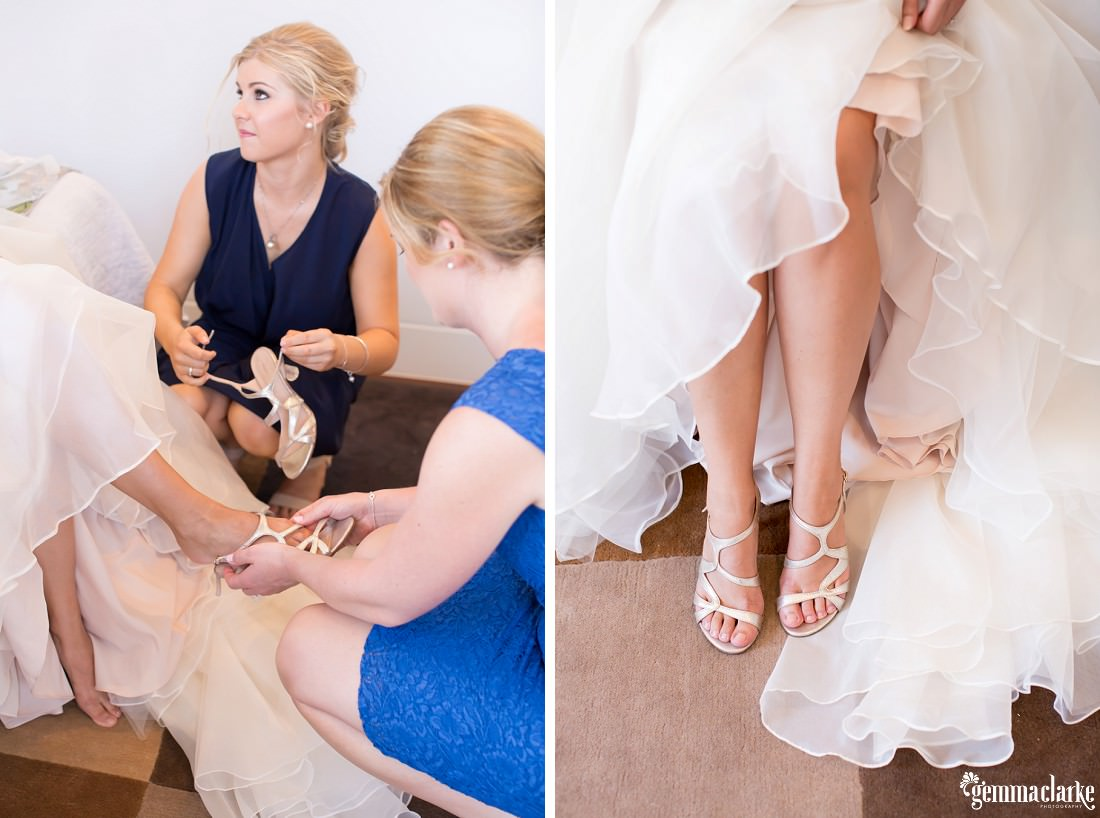 Bridesmaids helping a bride into her shoes