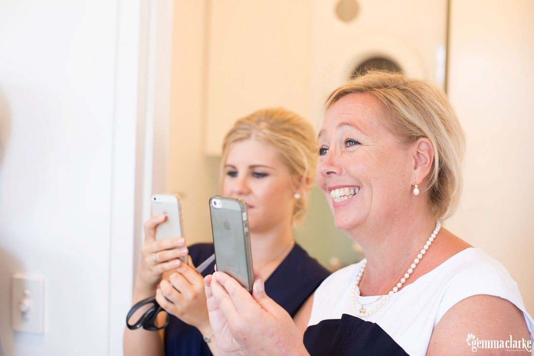 A bride's mother and bridesmaid taking photos with their phones