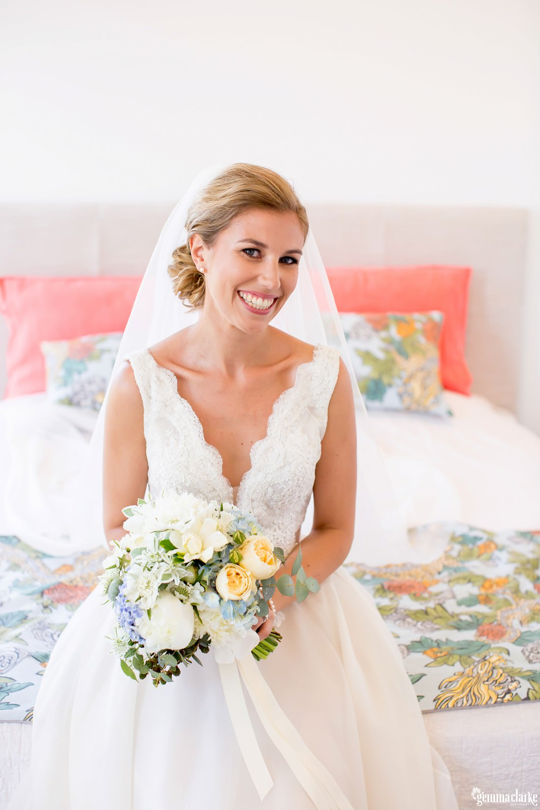 A smiling bride sitting on a bed