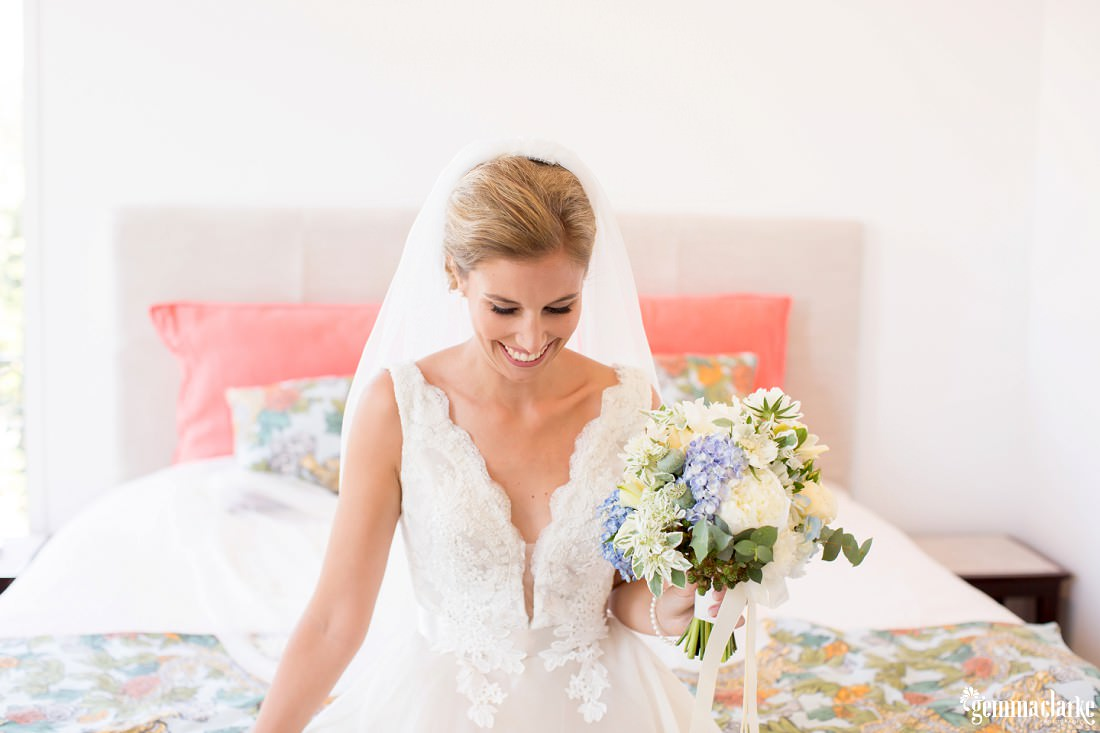 A smiling bride sitting on a bed holding a bouquet