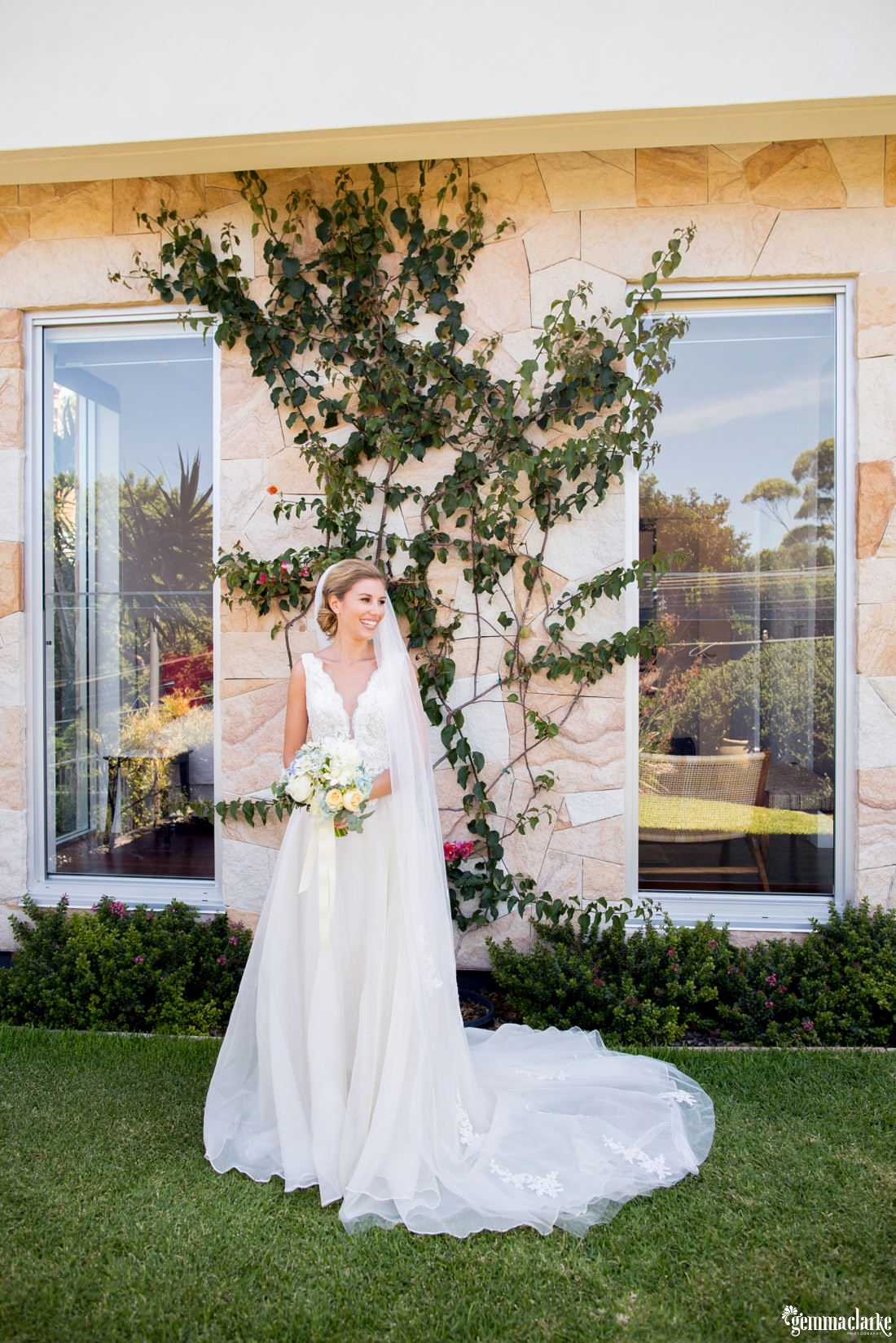 A bride posing in a garden in front of a house