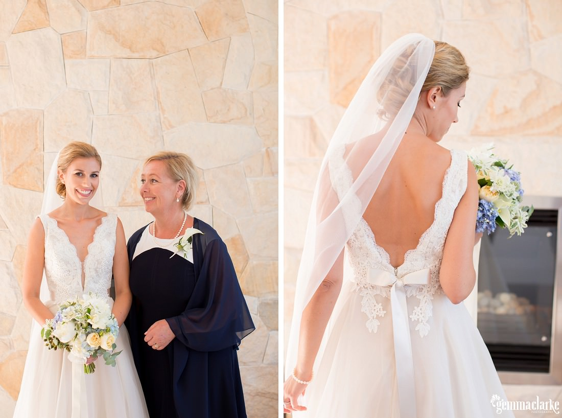 A bride's mother smiles at her, and the back of a bride's dress and veil
