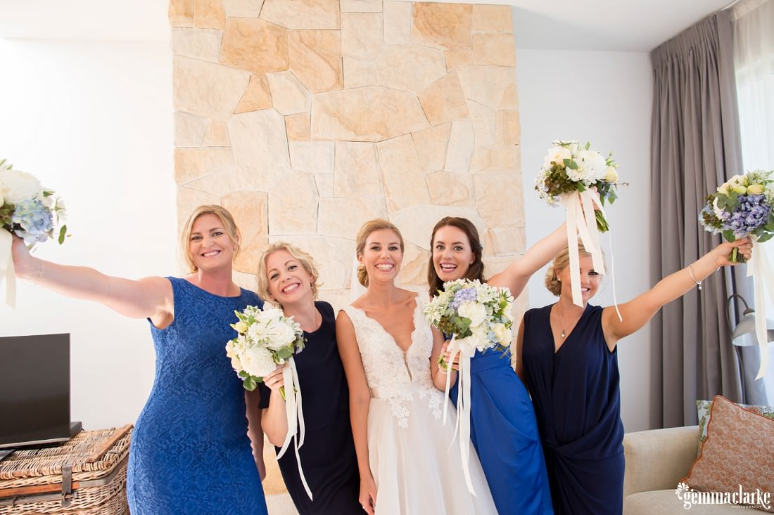 A bride and her bridesmaids smiling and holding up their bouquets