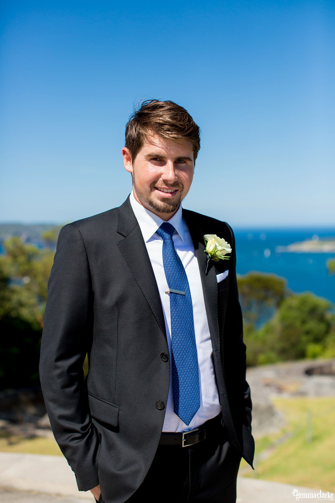 A groom in a dark suit with white shirt and blue tie stands with the Harbour in the background