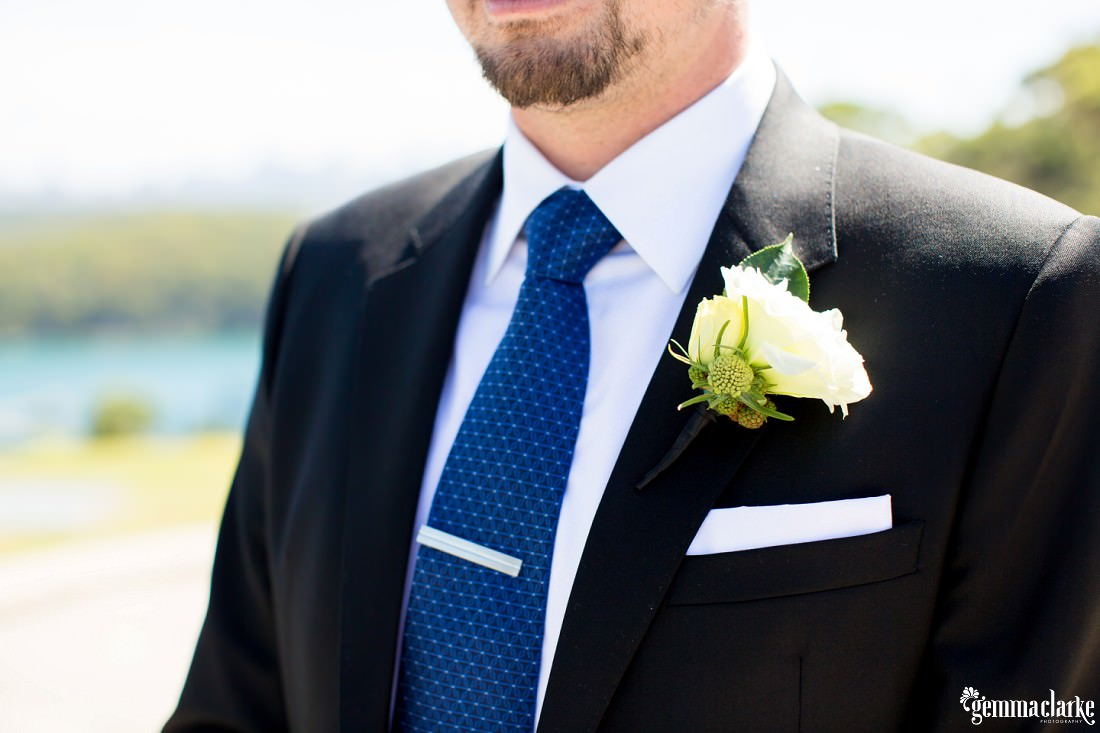A closeup of a groom's accessories - tie, tie pin, pocket square and floral buttonhole