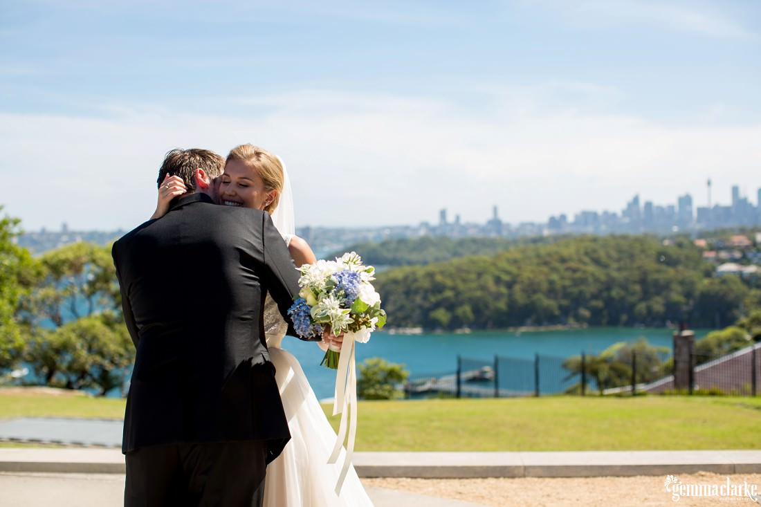 A bride and groom embrace with the city and harbour in the background