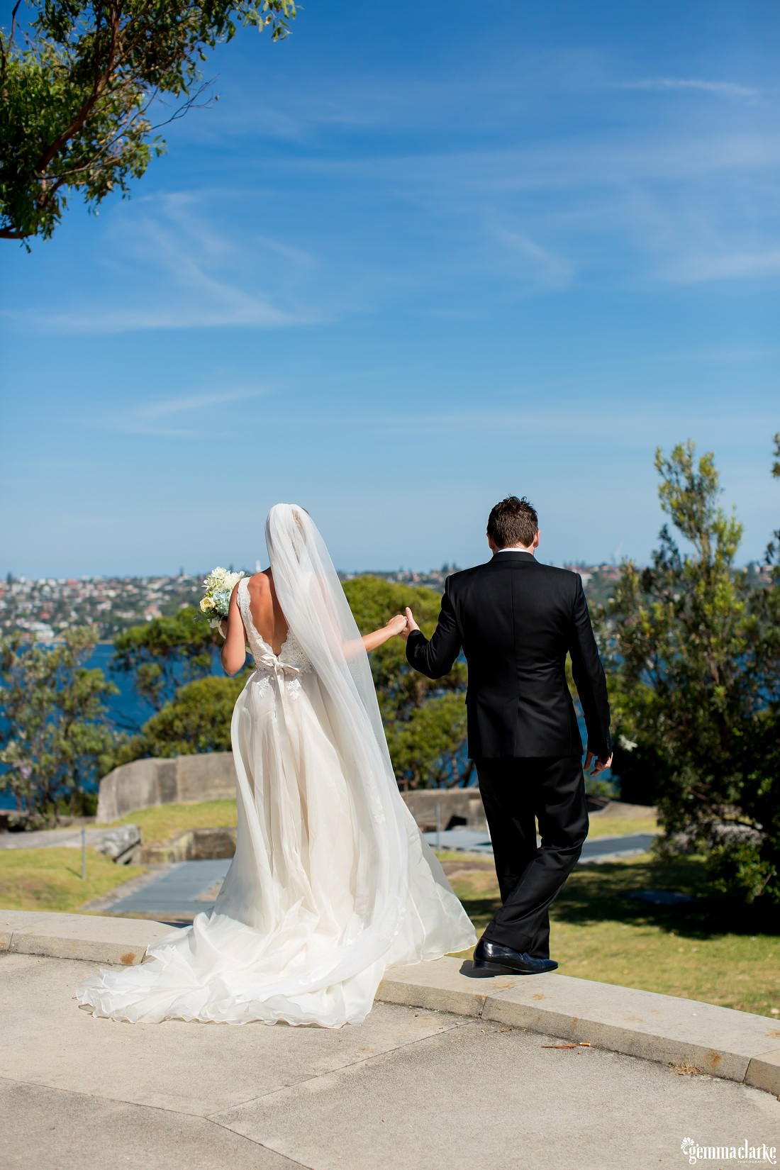 A bride and groom holding hands and walking down steps