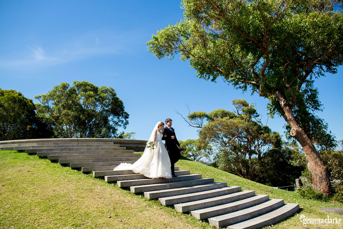 A bride and groom walking down steps arm in arm