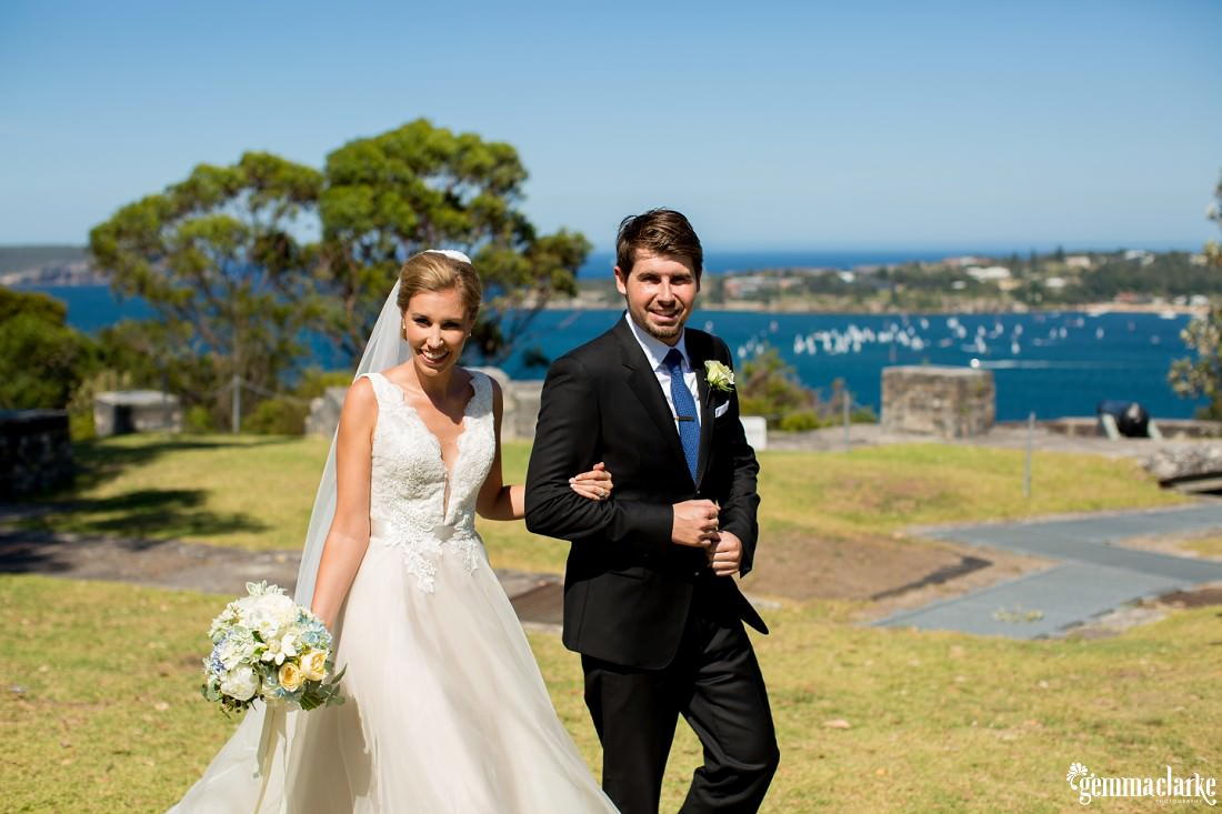 A smiling bride and groom walking arm in arm