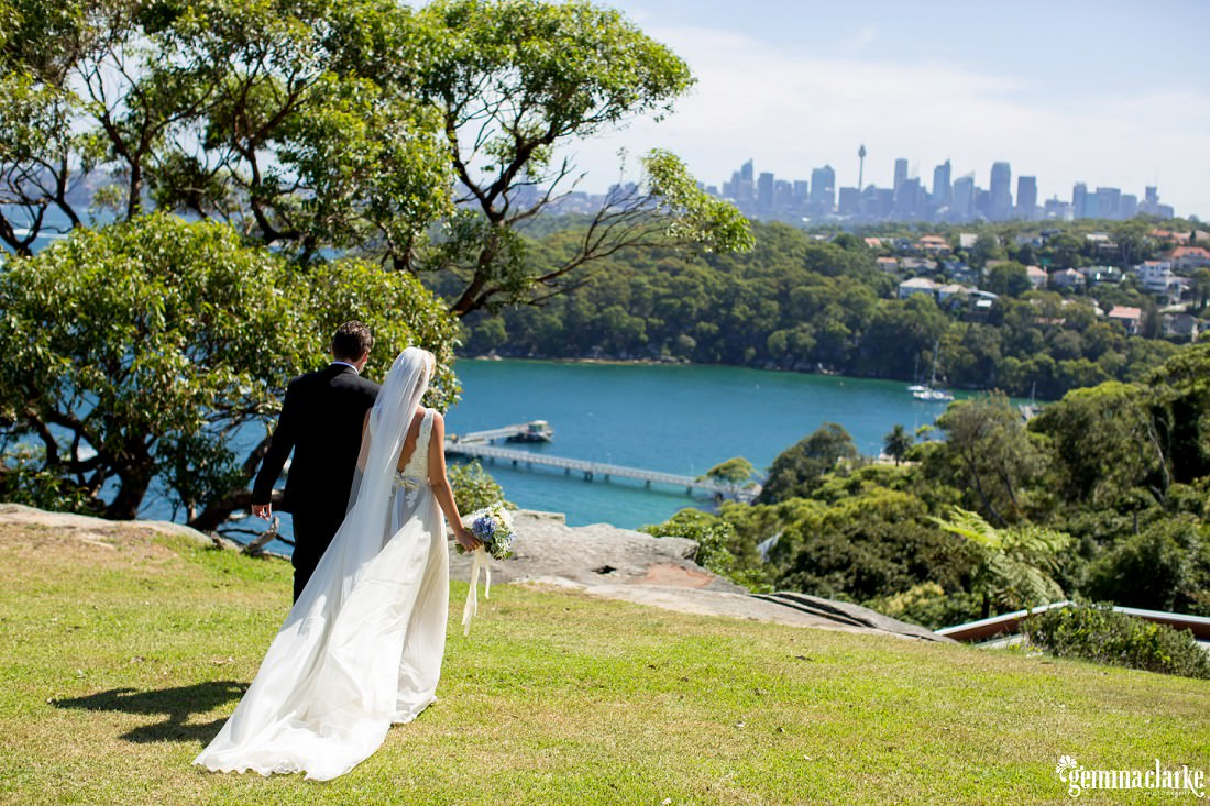 A bride and groom walking across grass arm in arm with the city and Harbour in the background