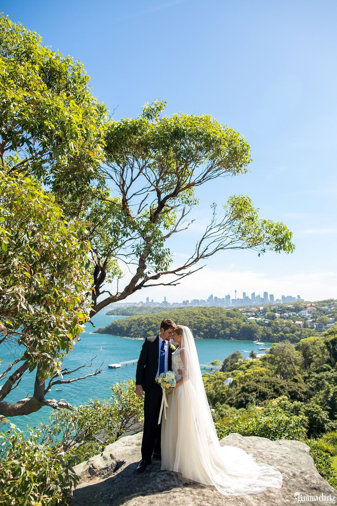 A bride and groom share an eskimo kiss will standing on a large rock near a tree with the city and harbour in the background