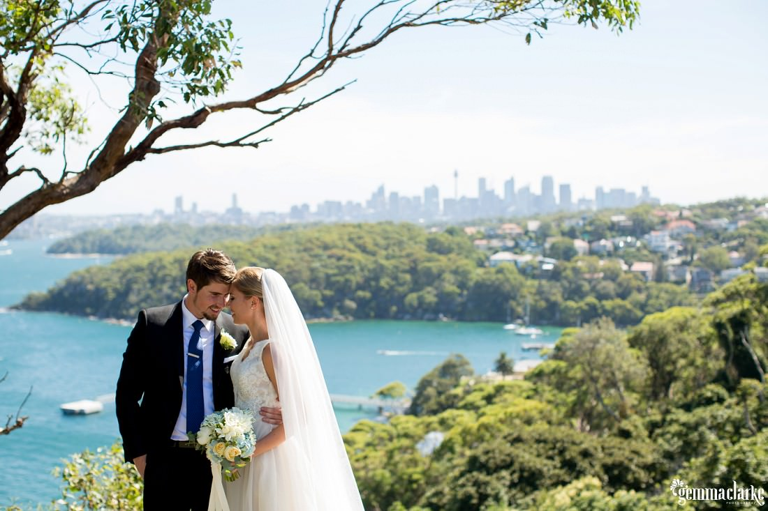 A groom with his arm around his bride with the city and harbour in the background