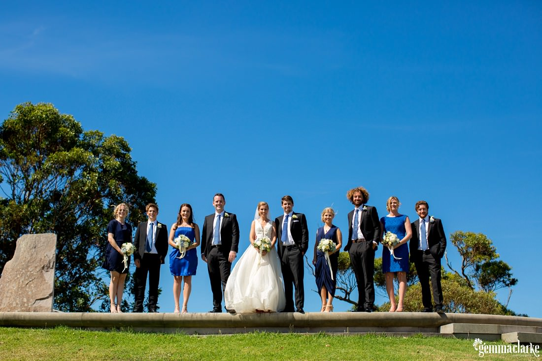 A bridal party standing against the background of a deep blue sky