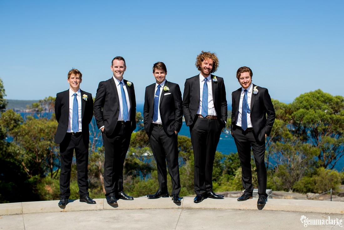 A groom and groomsmen standing on a ledge with their hands in their pockets