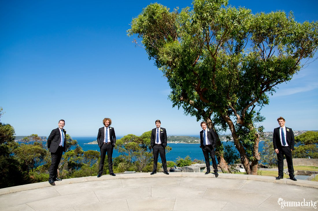 A groom and groomsmen stand spaced apart around a ledge with the harbour in the background