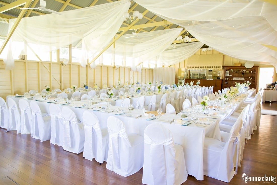 The inside of Athol Hall with white tables and chairs setup for a wedding reception