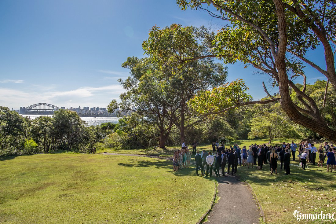 Wedding guests standing in the shade of trees with the Sydney Harbour Bridge in the background
