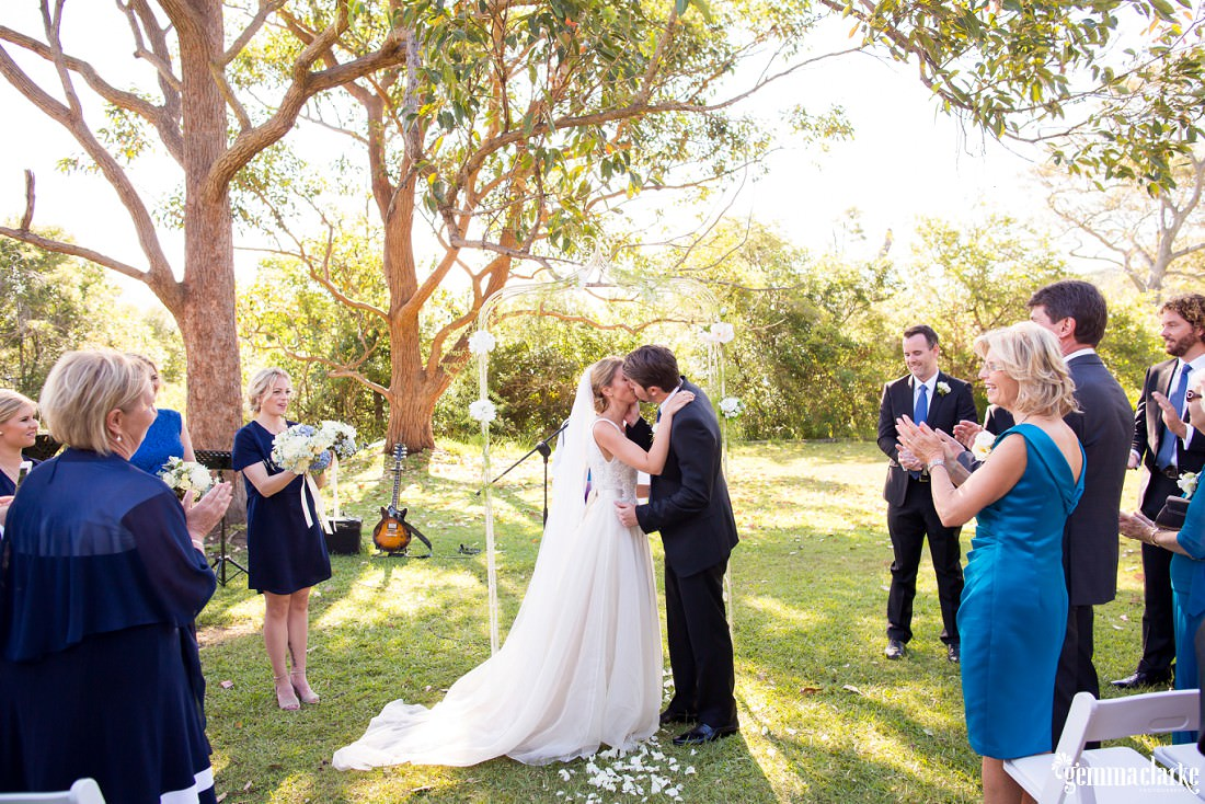 A bride and groom kiss at their wedding ceremony as their guests clap