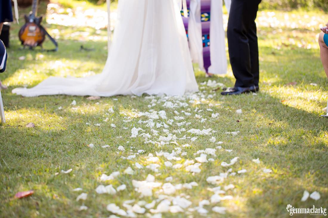 "A low shot of the flower petal ""aisle"" leading towards the bride and groom"