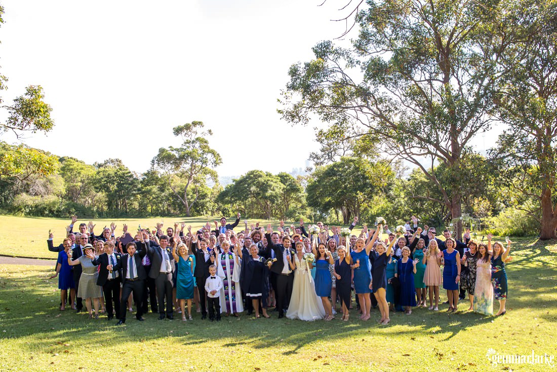 A group shot of a wedding party and their guests outside Athol Hall